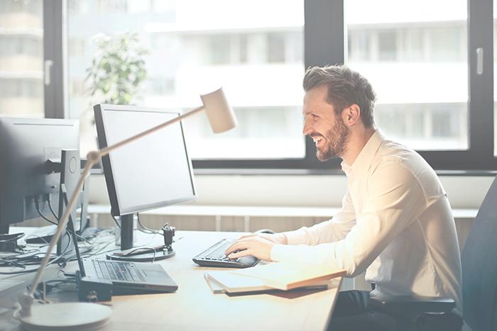 man arbetar på dator för att uppnå mål inom kundupplevelsen